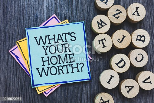 Handwriting text What s is Your Home Worth question. Concept meaning Value of a house Property Cost Price Rate Black wooden deck written sticky note beside some round woody alphabets