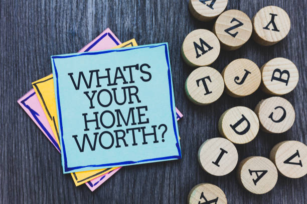 Handwriting text What s is Your Home Worth question. Concept meaning Value of a house Property Cost Price Rate Black wooden deck written sticky note beside some round woody alphabets. stock photo