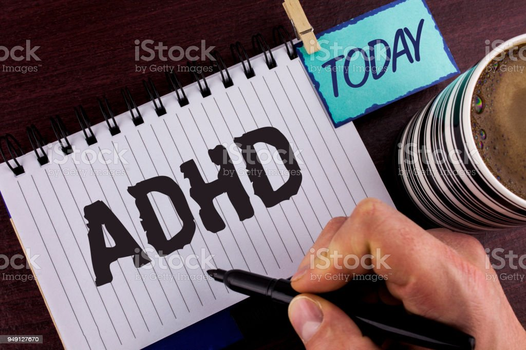 Handwriting text writing Adhd. Concept meaning Learning made easier for children teaching no more a difficult task written by Man on Notepad holding Marker in Hand wooden background Today Cup. stock photo