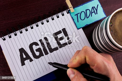 istock Handwriting text writing Agile Motivational Call. Concept meaning Develop an agility towards technological chnage written by Man on Notepad holding Marker in Hand wooden background Today Cup. 949131924