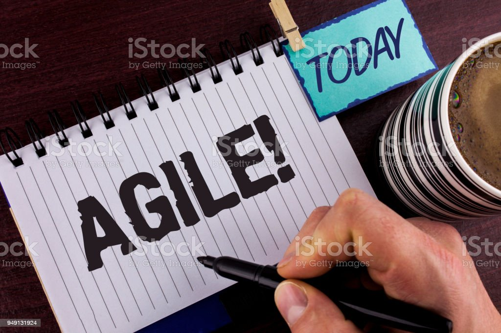 Handwriting text writing Agile Motivational Call. Concept meaning Develop an agility towards technological chnage written by Man on Notepad holding Marker in Hand wooden background Today Cup. stock photo