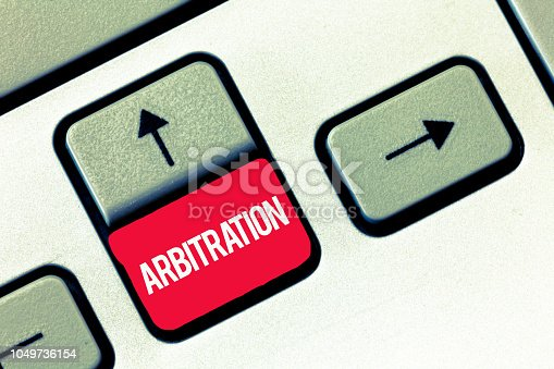 istock Handwriting text writing Arbitration. Concept meaning Use of an arbitrator to settle a dispute Mediation Negotiation 1049736154