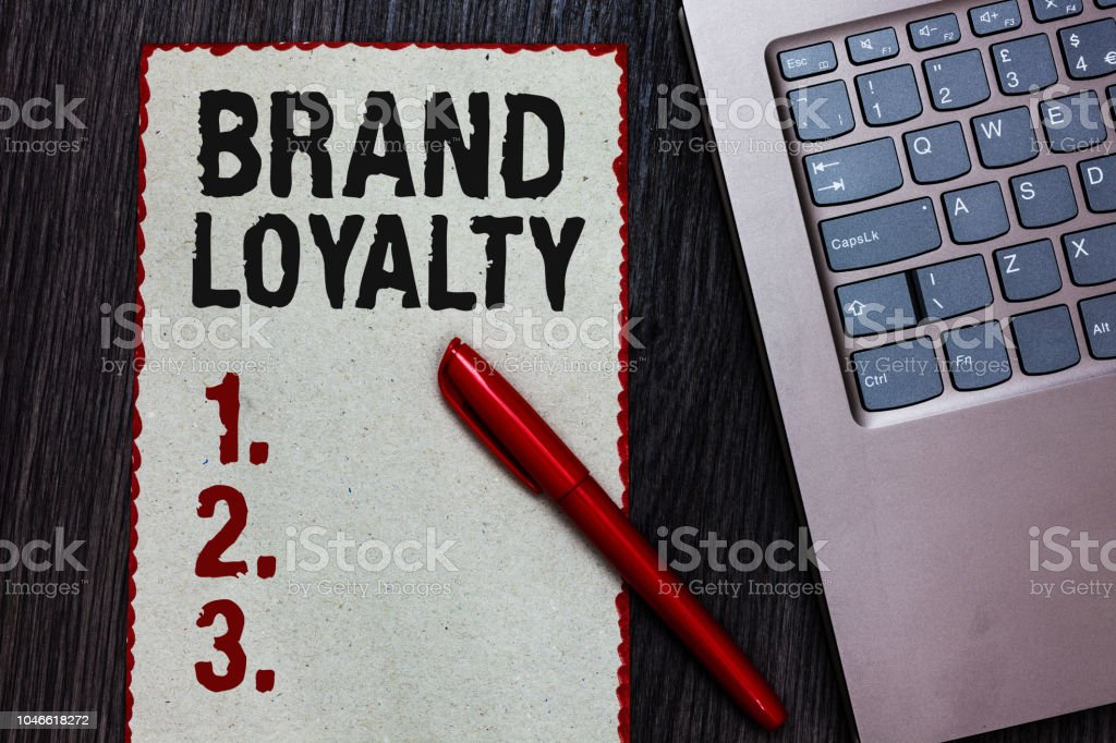 Handwriting text writing Brand Loyalty. Concept meaning Repeat Purchase Ambassador Patronage Favorite Trusted Piece paper red borders black marker computer keyboard wooden background. stock photo