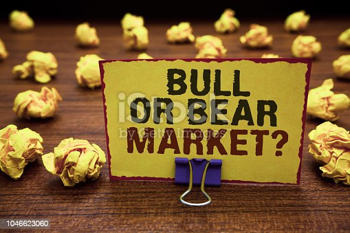 Handwriting text writing Bull Or Bear Market question. Concept meaning asking someone about his marketing method Yellow sticky card clipped text notice crumpled paper balls wood table