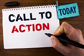 istock Handwriting text writing Call To Action. Concept meaning most important part of online digital marketing campaign written by Man on Notepad holding Marker on wooden background Today Clip. 946567222