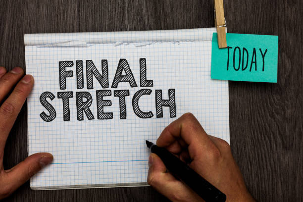 Handwriting text writing Final Stretch. Concept meaning Last Leg Concluding Round Ultimate Stage Finale Year ender Open notebook clothespin holding reminder clothespins clips wooden table. stock photo