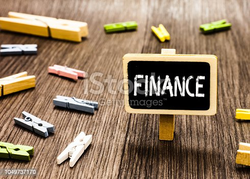 istock Handwriting text writing Finance. Concept meaning Management of large government companies money amount Provide funds Blackboard standing several clothespins disorganized messy wooden floor. 1049737170