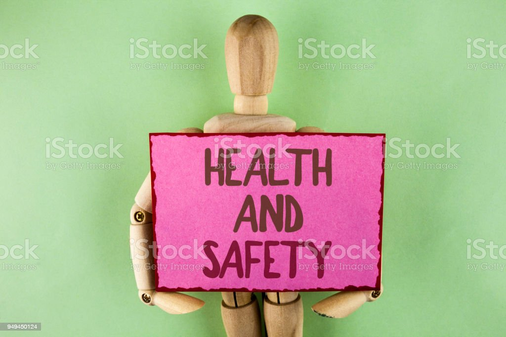 Handwriting text writing Health And Safety. Concept meaning being in good condition harmless Workouts Healthy food written on Sticky note paper holding by Wooden Robot Toy on plain background. stock photo