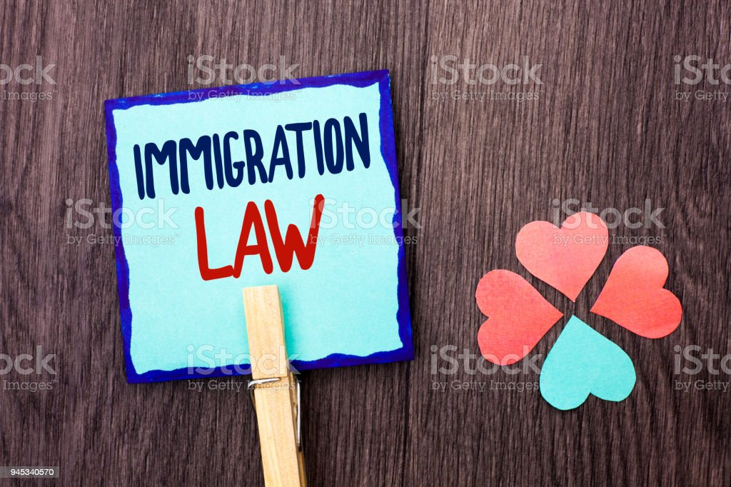 Handwriting text writing Immigration Law. Concept meaning National Regulations for immigrants Deportation rules written on Sticky Note Paper Holding With Clip on the wooden background Hearts. stock photo