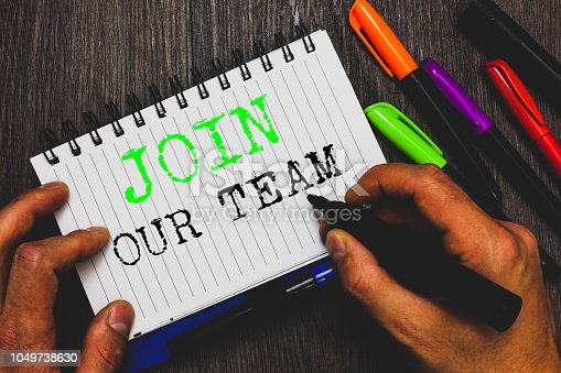 istock Handwriting text writing Join Our Team. Concept meaning Allied Associate Work with us New Employee Hired Enlist Man holding marker notebook paper communicating ideas Wooden background. 1049738630