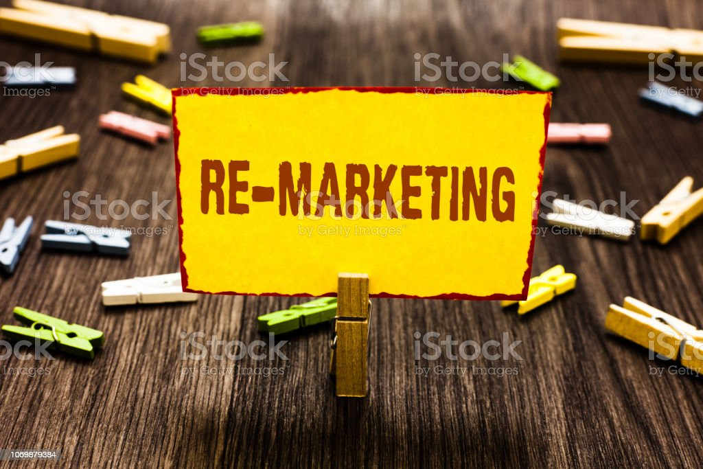 Handwriting text writing Re Marketing. Concept meaning Strategy to reach potential customers in your website Clothespin holding yellow paper note several clothespins wooden floor. stock photo