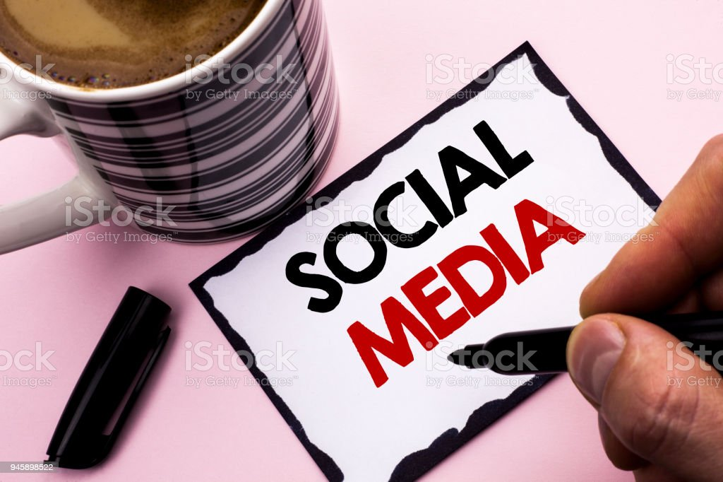 Handwriting text writing Social Media. Concept meaning Communication Chat Online Messaging Share Community Societal written by Man on Sticky Note paper holding Marker plain background Coffee Cup stock photo
