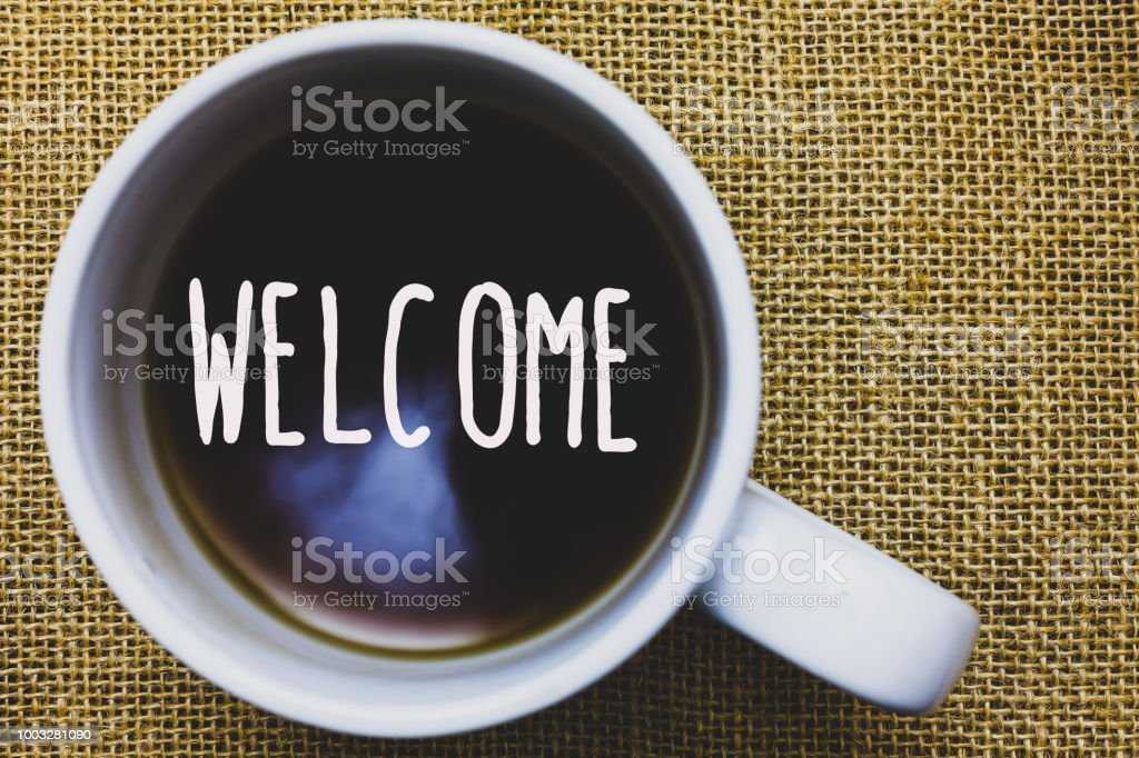 Handwriting text writing Welcome. Concept meaning Warm salutation acknowledgement for someone amiable loved thanked Mug coffee thoughts ideas creative inspirations nice mat black shadow. stock photo