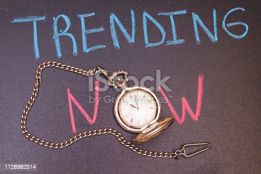 1128981457 istock photo handwriting trending now on chalkboard with colorful chalk and antique watch 1128982514