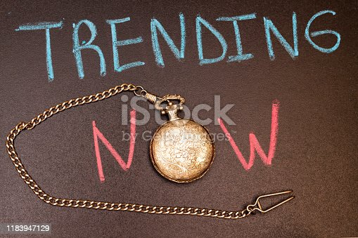 1128981457 istock photo handwriting trending now on chalkboard with colorful chalk and antique watch 1183947129