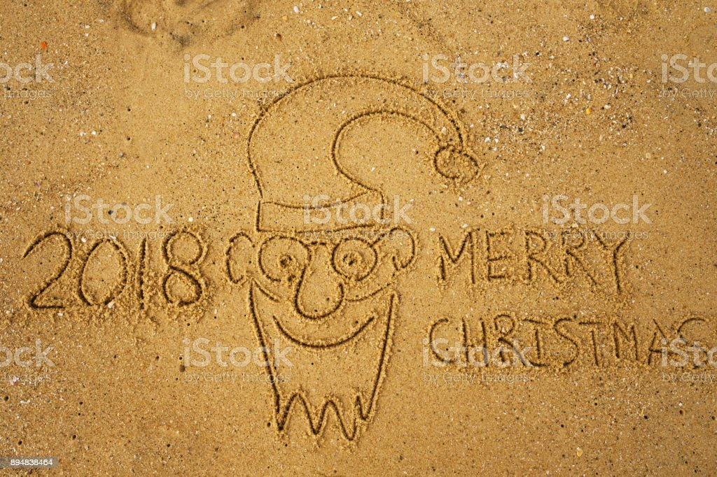 Handwriting words MERRY CHRISTMAS 2018 on sand of beach and funny face of santa claus. stock photo