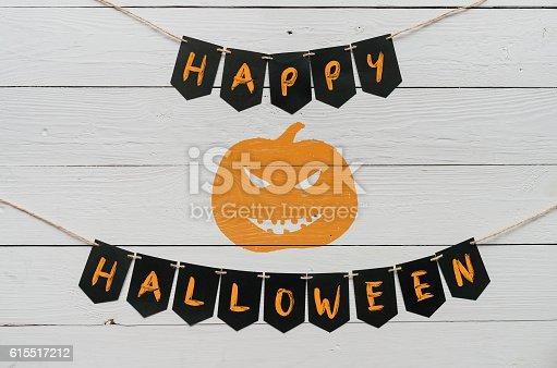 istock Handwritten happy halloween banner lettering, cut pumpkin 615517212