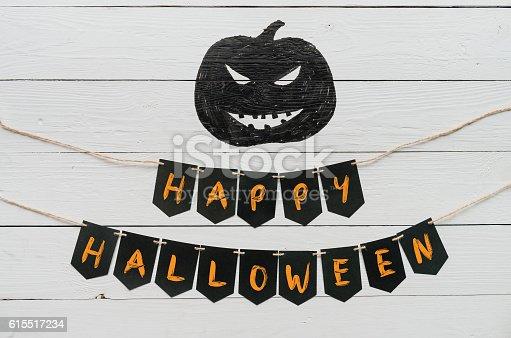 istock Handwritten happy halloween banner lettering, cut pumpkin 615517234