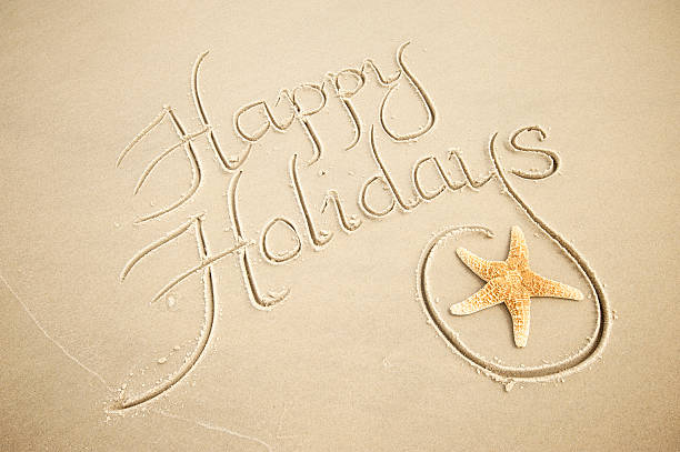 Handwritten Happy Holidays Greeting Message with Decorative Starfish in Sand stock photo
