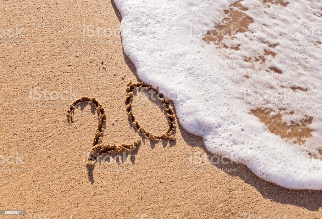 Handwritten inscription 20 on the sand with foamy wave stock photo