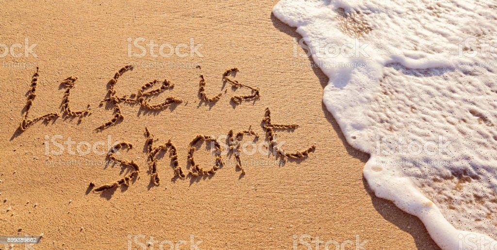 Handwritten inscription Life is Short on the sand with flushing foamy wave stock photo