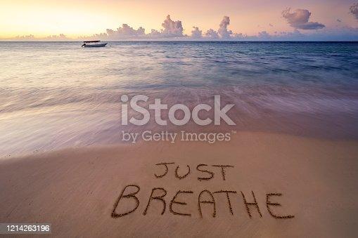 Handwritten Just breathe on sandy beach at sunset,relax and summer concept,Dominican republic beach.