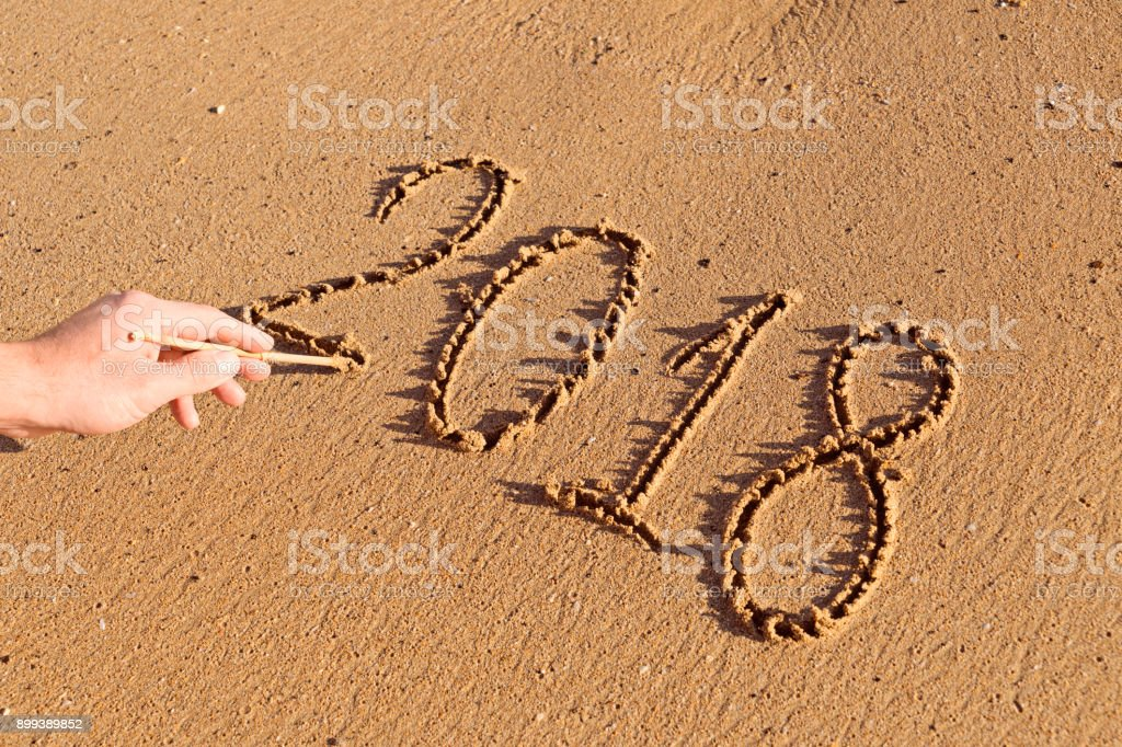 Handwritten numbers on the sand 2018 with male hand stock photo