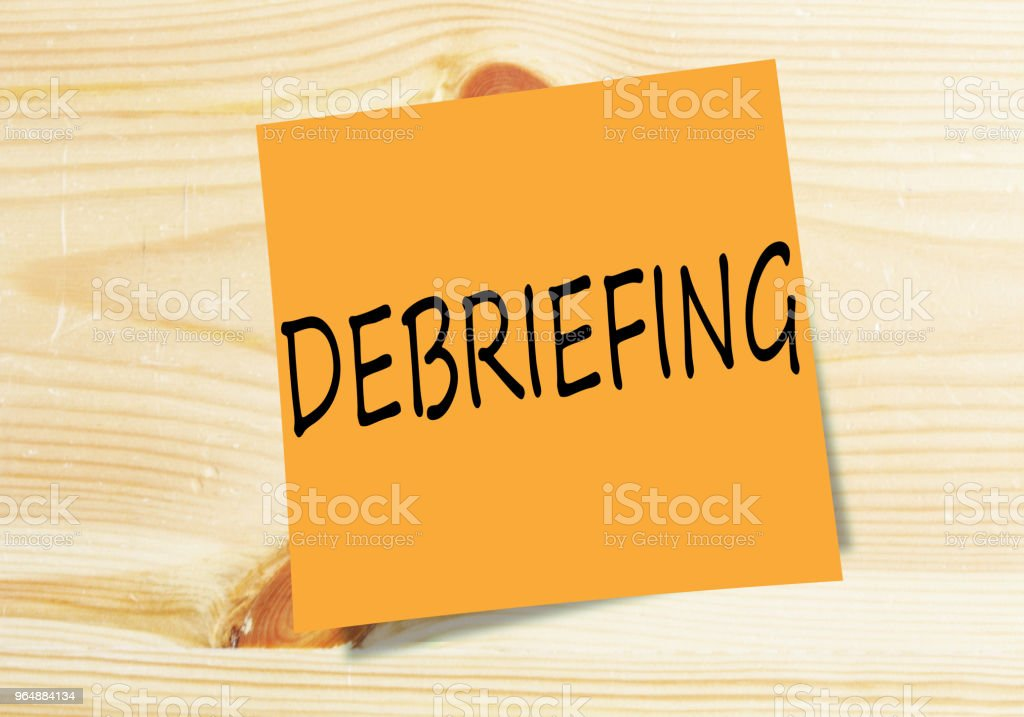 DEBRIEFING handwritten on orange small paper on wood texture background royalty-free stock photo