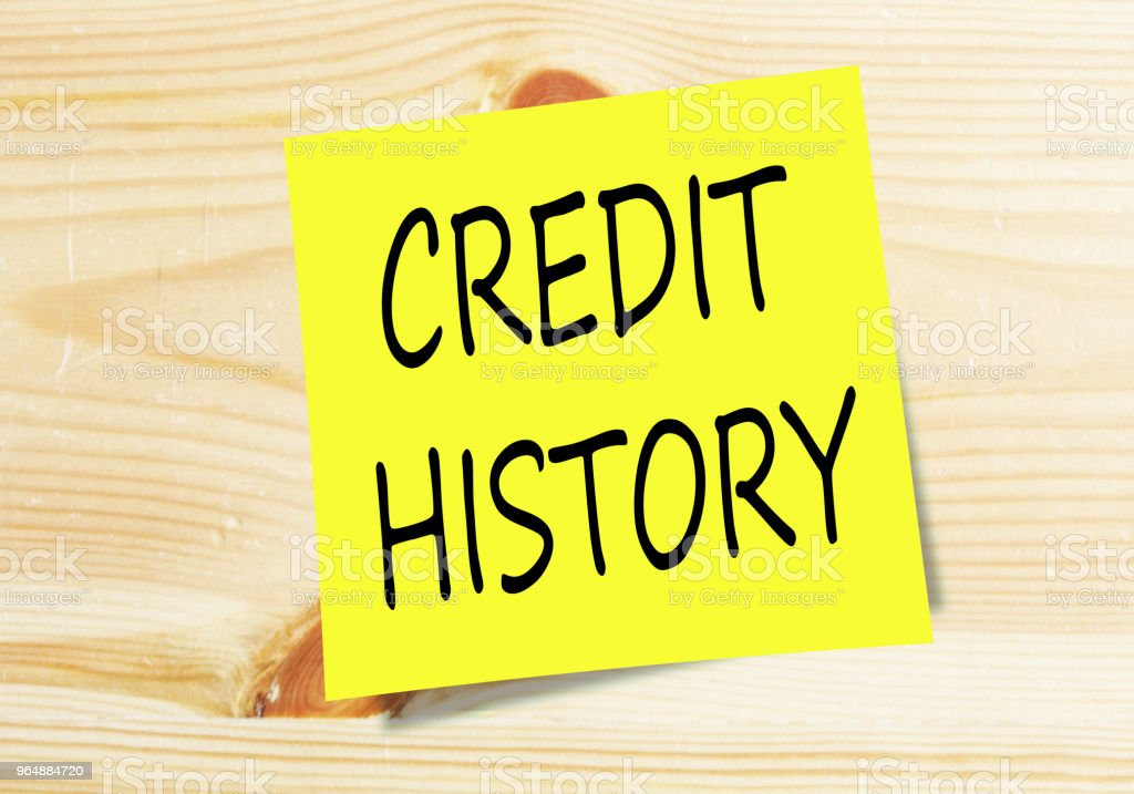 CREDIT HISTORY handwritten on small yellow paper on wood texture background royalty-free stock photo