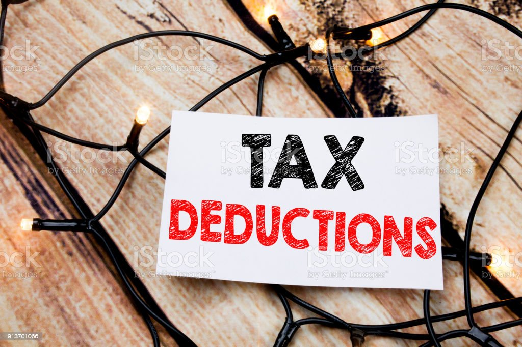 Handwritten text caption showing Tax Deductions. Business concept writing for Finance Incoming Tax Money Deduction written on sticky note paper on the wooden background. stock photo