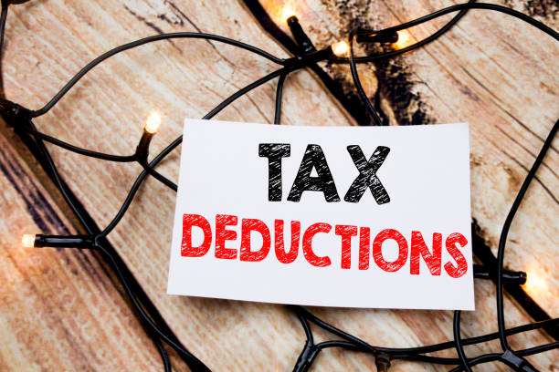 handwritten text caption showing tax deductions. business concept writing for finance incoming tax money deduction written on sticky note paper on the wooden background. - fare una pausa foto e immagini stock