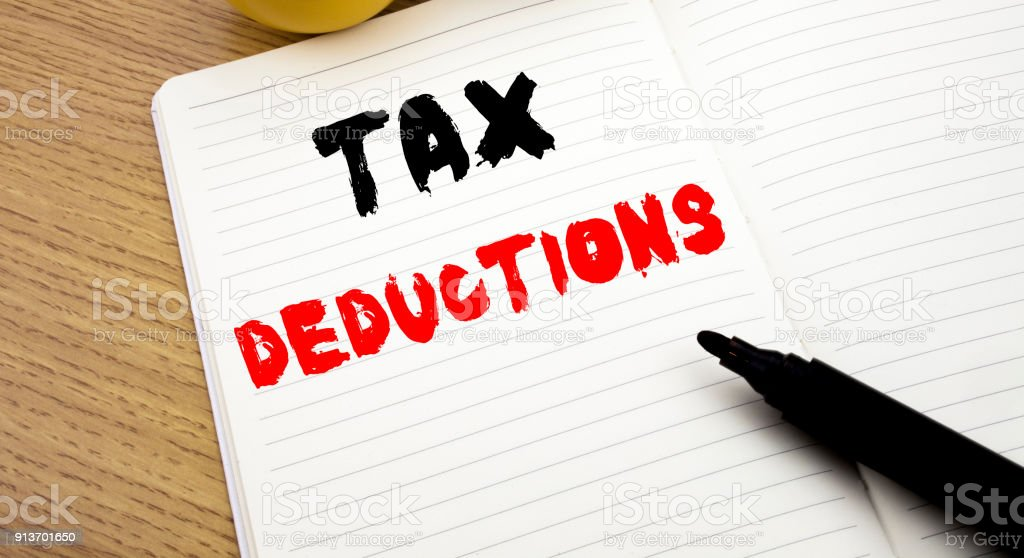 Handwritten text caption showing Tax Deductions. Business concept writing for Finance Incoming Tax Money Deduction written on notebook with copy space on book background with marker pen stock photo
