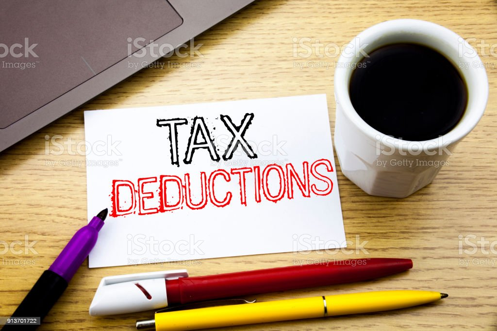 Handwritten text caption showing Tax Deductions. Business concept writing for Finance Incoming Tax Money Deduction written on notebook book on the wooden background in the Office with laptop coffee stock photo