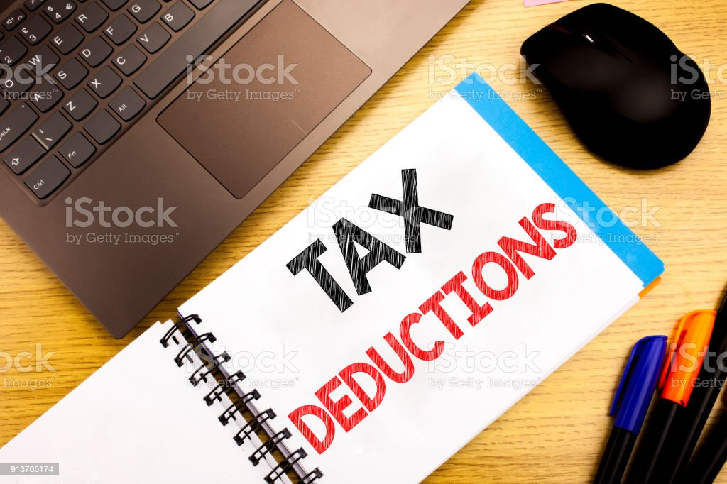 Handwritten text caption showing Tax Deductions. Business concept writing for Finance Incoming Tax Money Deduction written on notepad with copy space on old wood wooden with pen computer stock photo