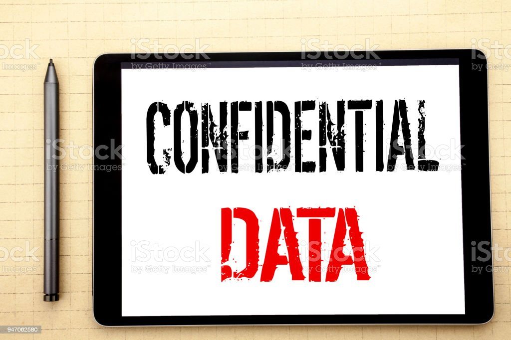 Handwritten text showing Confidential Data. Business concept writing for Secret Protection Written on tablet computer screen, white background in  office space view with pencil marker stock photo