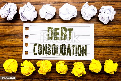 Handwritten text showing Debt Consolidation. Business concept for Money Loan Credit Written on sticky, wooden with sticky, many folded paper white and yellow for difference or collaboration
