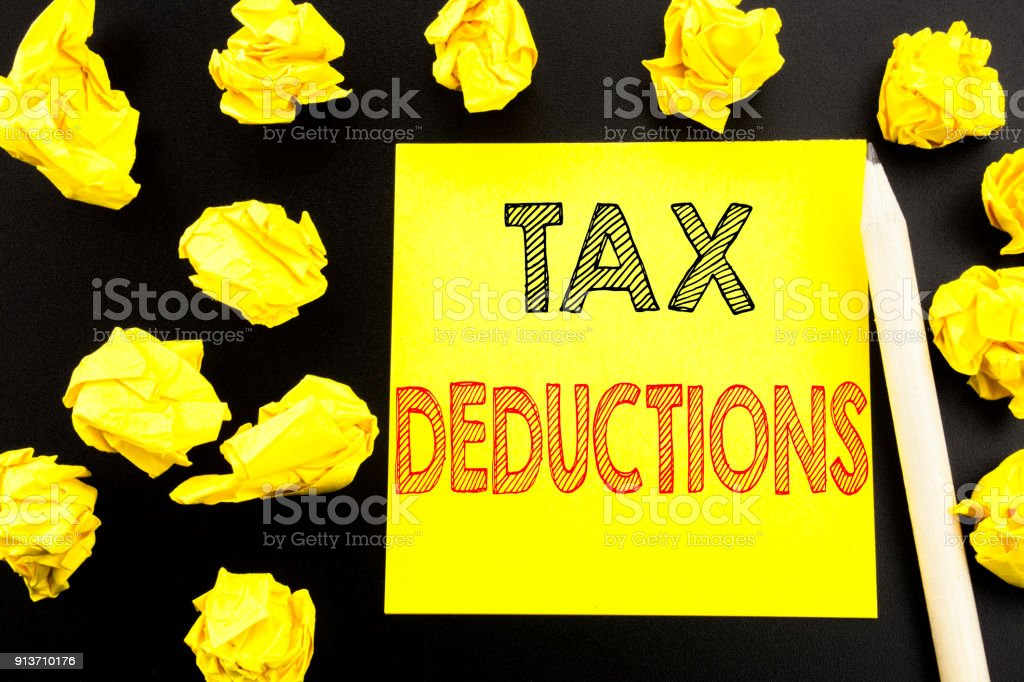 Handwritten text showing Tax Deductions. Business concept writing for Finance Incoming Tax Money Deduction written on sticky note paper on the black background. Folded yellow papers on the background stock photo