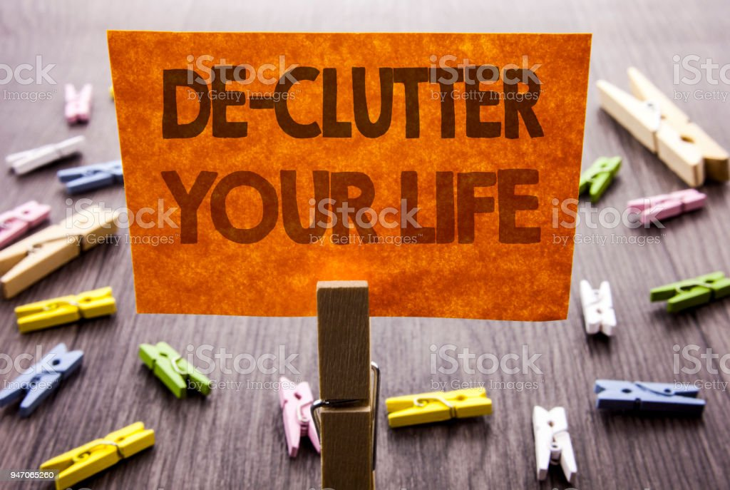 Handwritten text sign showing De-Clutter Your Life. Business concept for Free Less Chaos Fresh Clean Routine written on sticky Note on the wooden background. stock photo