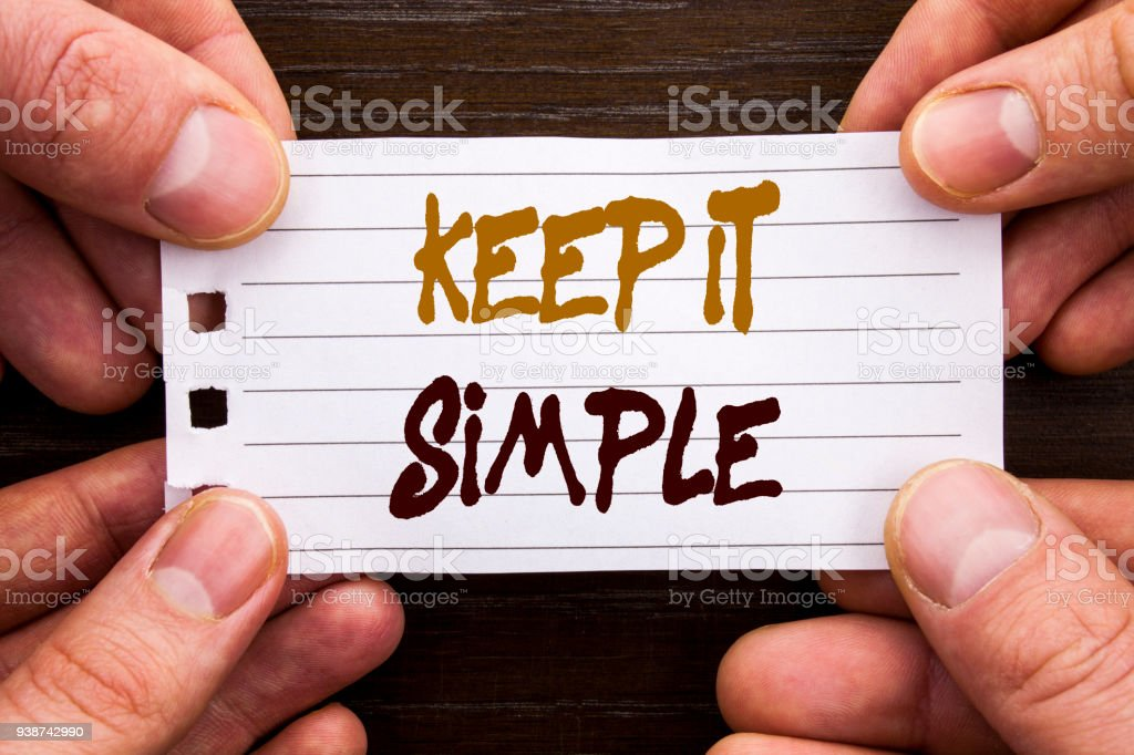 Handwritten text sign showing Keep It Simple. Business concept for Simplicity Easy Strategy Approach Principle written on Sticky Note Paper Holding Hand with Finger. stock photo