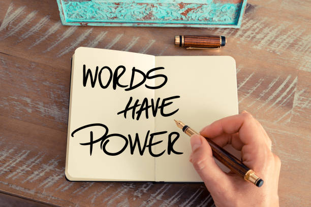 Handwritten text Words Have Power Retro effect and toned image of a woman hand writing a note with a fountain pen on a notebook. Handwritten text Words Have Power as success and evolution concept image single word stock pictures, royalty-free photos & images