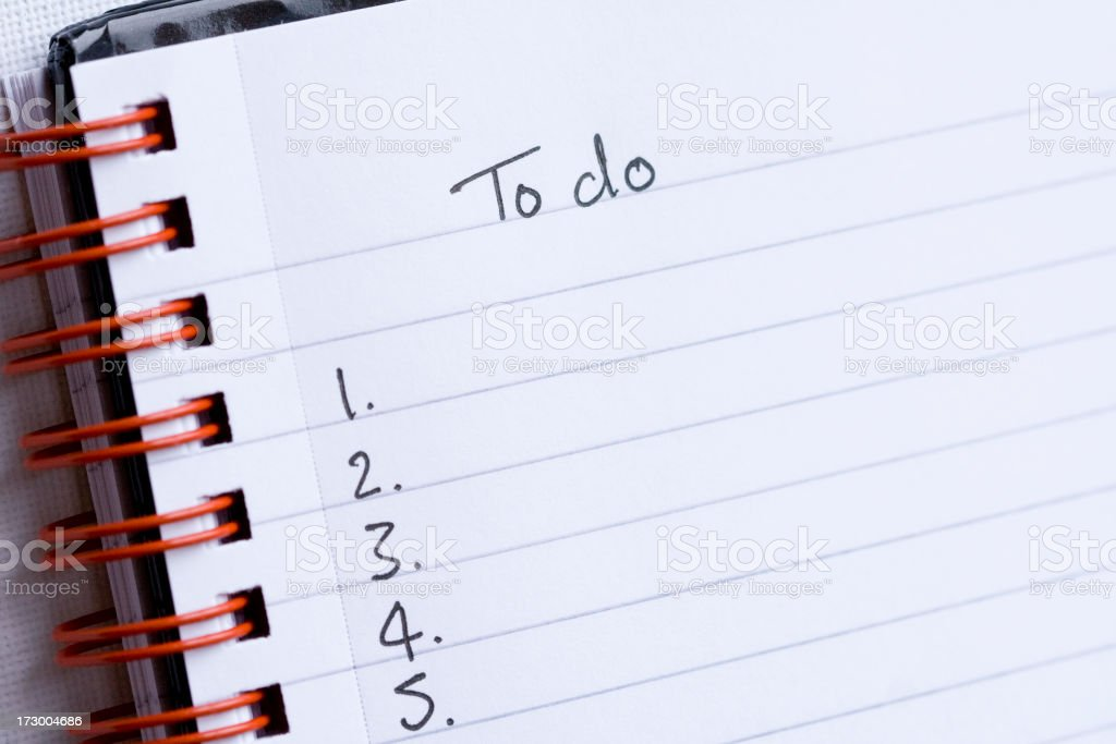 to do list on lined white note pad with red metal binder