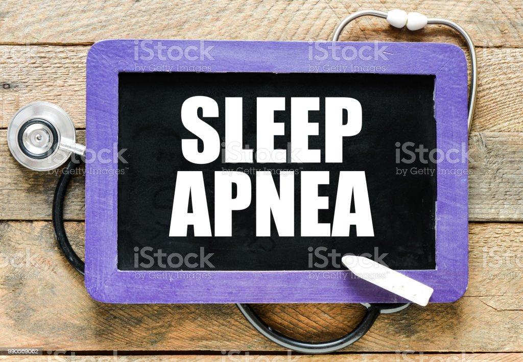 SLEEP APNEA handwritten with white chalk on a blackboard on wood background stock photo