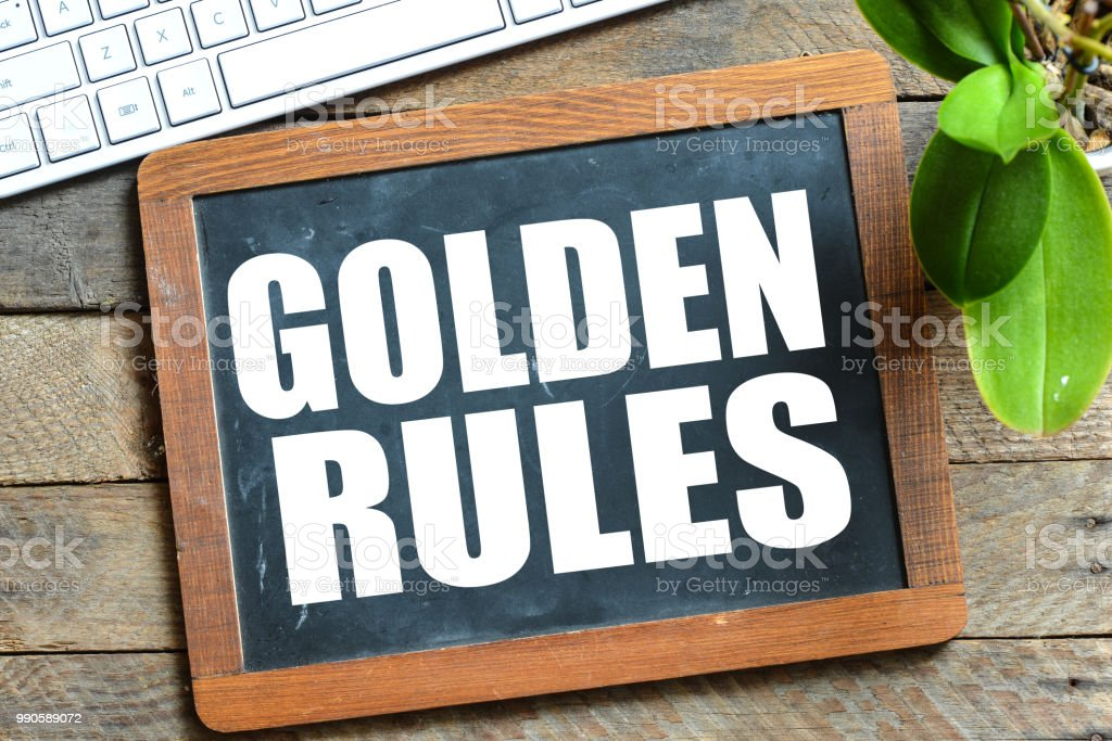 GOLDEN RULES handwritten with white chalk stock photo
