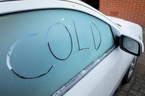 """handgeschriebene wort """"kalt"""" in der frost eine gefrorene autofenster, farbe des fahrzeugs ist grau und es ist in einem wohngebiet geparkt. - auto trennwand stock-fotos und bilder"""