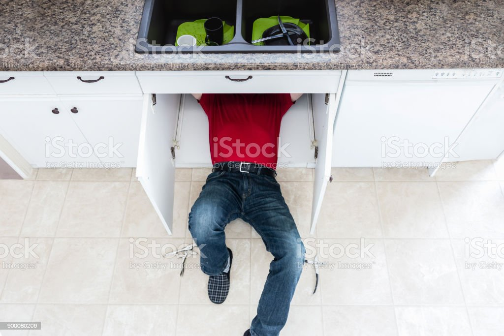handy man fixing a leak under the kitchen counter. stock photo