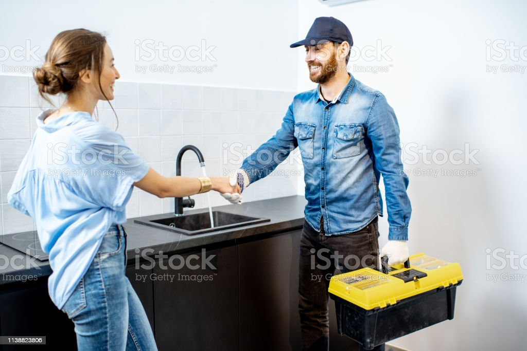 Handy man having a deal with young woman client after the repairment...