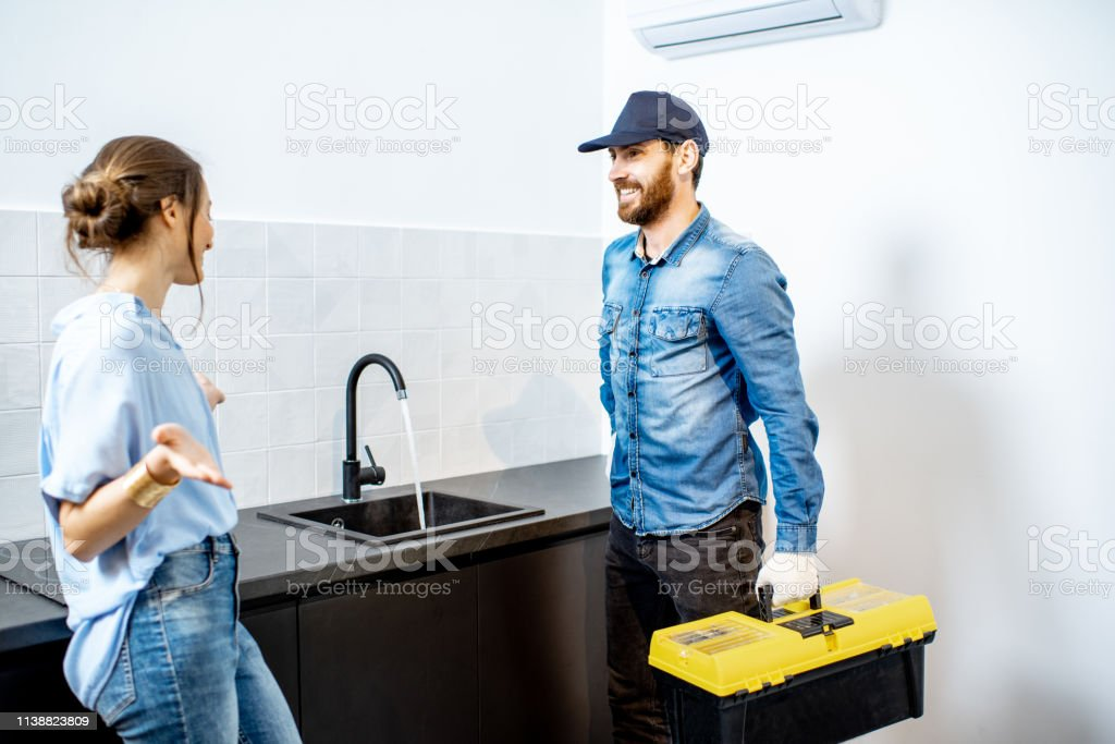 Handy man talking with young woman client after the repairment on the...