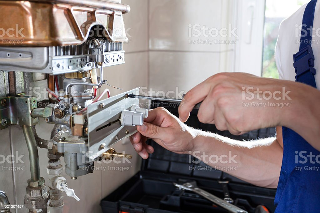 Handyman adjusting gas water heater stock photo