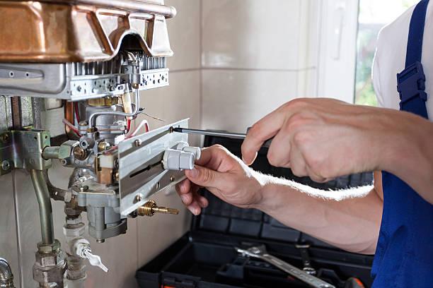 Handyman adjusting gas water heater stock photo