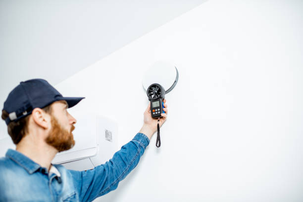 Handyman checking of air ventilation Handyman checking the speed of air ventilation with measuring tool on the white wall background wind stock pictures, royalty-free photos & images